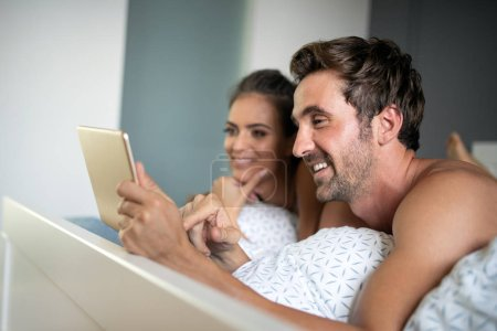 Photo for Cheerful couple looking a tablet together and laughing while lying on the bed - Royalty Free Image