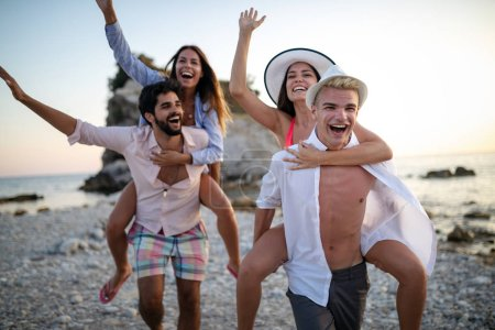 Photo for Cheerful couples friends enjoying weekend and having fun on beach - Royalty Free Image