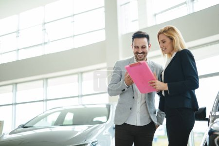Portrait of happy handsome customer buying new car