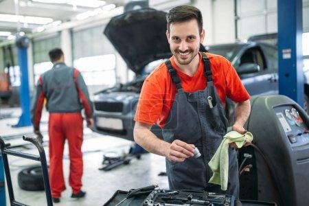 Photo pour Jeune mécanicien automobile travaillant dans le garage. Service de réparation . - image libre de droit