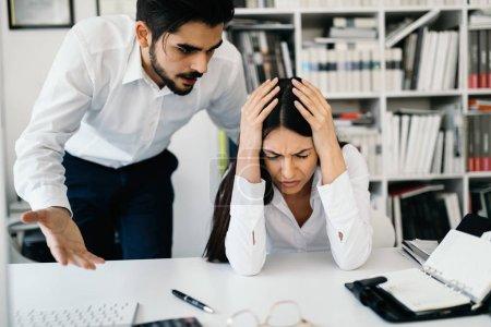 Foto de Empresario gritándole a una colega en el escritorio en la oficina - Imagen libre de derechos