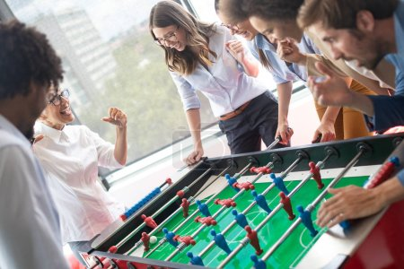Photo for Coworkers playing table football and ralaxing on break from work - Royalty Free Image