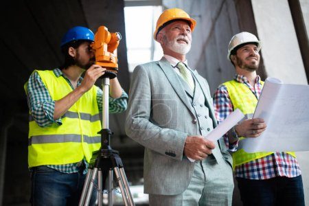 Photo for Engineer and construction site manager working with blueprints and plans - Royalty Free Image