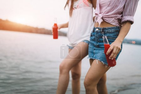 Photo for Two women friends laughing and hugging outdoors together - Royalty Free Image
