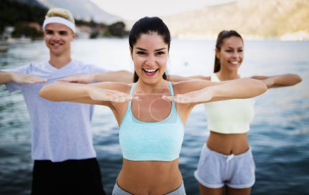 Fit group of young people exercising outdoor. Smil...