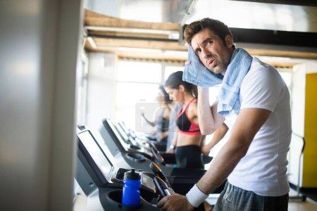 Foto de Sudoroso después de un gran ejercicio. Guapos jóvenes en ropa deportiva azotando el sudor con su toalla - Imagen libre de derechos