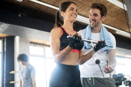 Photo for Young beautiful fit woman doing exercises with personal trainer - Royalty Free Image