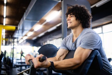Photo for Happy fit man doing exercises in gym - Royalty Free Image
