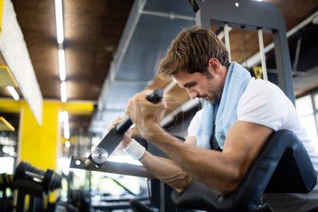 Photo pour Sport, fitness, musculation, style de vie et concept de personnes - l'homme fait de l'exercice dans une salle de gym - image libre de droit