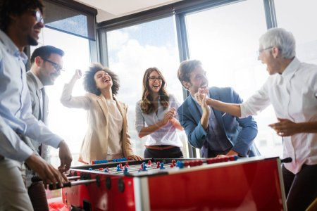Photo for Multicultural business people celebrating win while playing table football together - Royalty Free Image
