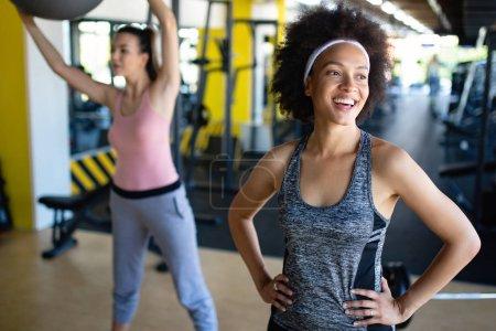 Photo pour Belles femmes en forme travaillant ensemble dans la salle de gym - image libre de droit