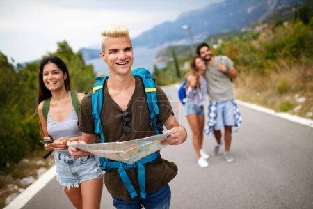 Photo pour Groupe d'amis voyageur marchant et s'amusant. Style de vie de voyage et concept de vacances saisonnières - image libre de droit