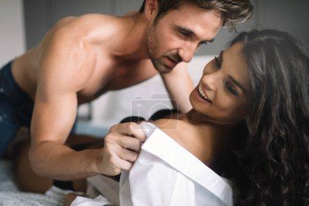 Photo pour Jeune couple érotique étant intime dans la chambre. Amoureux sensuels faisant l'amour - image libre de droit