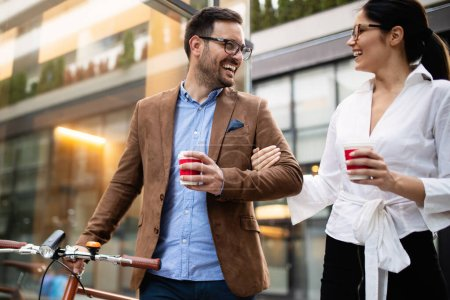 Photo for Happy business people discussing and smiling while walking together outdoor - Royalty Free Image