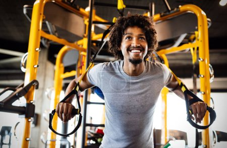 Photo for Man doing push ups training with trx fitness straps in the gym. Workout healthy lifestyle sport concept - Royalty Free Image