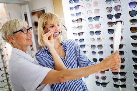 Photo pour Soins de santé, vision et concept de vision. Heureuse jeune femme qui choisit des lunettes au magasin d'optique - image libre de droit