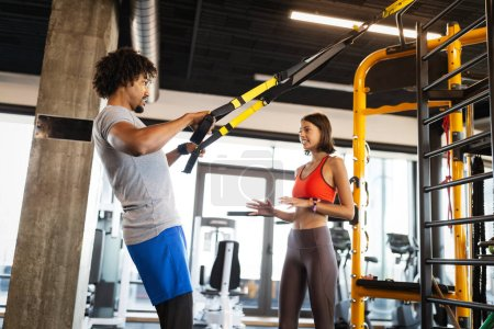 Photo for Fitness instructor exercising with fit people at the gym. - Royalty Free Image
