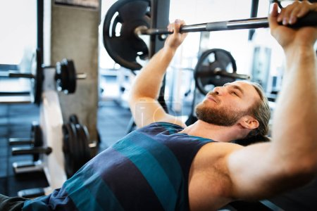 Photo for Healthy life and gym exercise. Handsome fit man working out in health club - Royalty Free Image