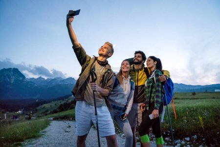 Photo for Group of young friends hiking in countryside. Multiracial happy people travelling in nature - Royalty Free Image