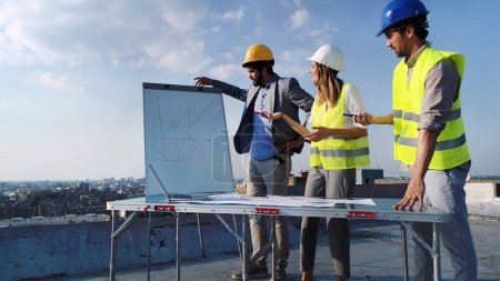 Photo for Team of architects and engineers people in group on construciton site check documents - Royalty Free Image