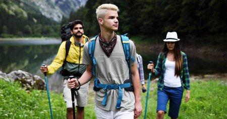 Foto de Gente de excursión. Grupo de amigos excursionistas felices trekking como parte de la actividad al aire libre estilo de vida saludable - Imagen libre de derechos