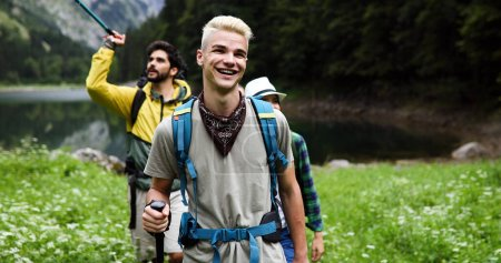 Photo for Friends hiking together outdoors exploring the wilderness and having fun - Royalty Free Image