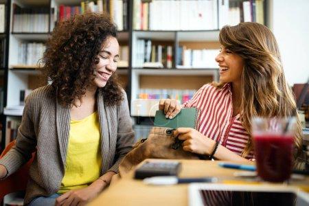 Photo pour Étudiants universitaires en coopération avec leur affectation à la bibliothèque. Groupe de jeunes lisant des livres. - image libre de droit