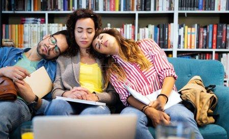 Photo pour Groupe de jeunes étudiants fatigués étudiant, apprenant pour l'examen à la bibliothèque. Éducation, études, concept universitaire. - image libre de droit