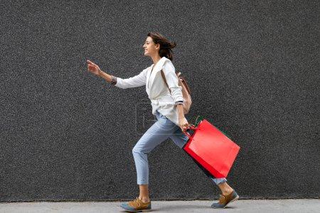Photo pour Portrait de jeune femme souriante heureuse énergique avec des sacs à provisions - image libre de droit