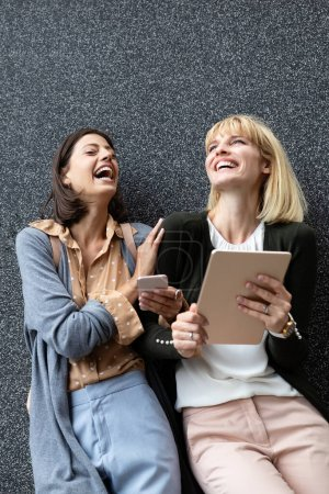 Photo for Smiling young women friends having fun with tablet outdoor - Royalty Free Image