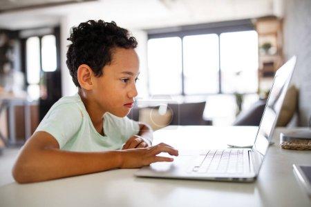 Photo pour Africain garçon passer du temps avec ordinateur portable et la technologie moderne - image libre de droit