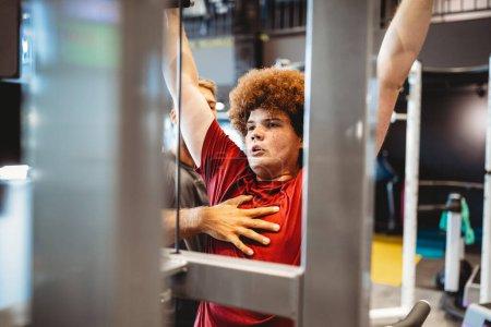 Foto de Hombre joven con sobrepeso con entrenador haciendo ejercicio en el gimnasio - Imagen libre de derechos
