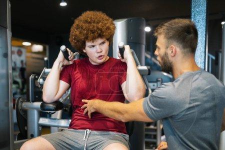 Foto de Sobrepeso joven gordito hombre ejercicio gimnasio con entrenador personal - Imagen libre de derechos