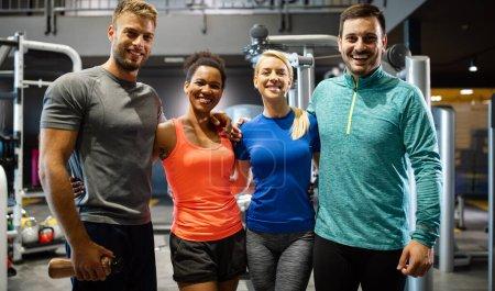 Photo pour Groupe de jeunes amis souriants et profiter du sport dans la salle de gym - image libre de droit