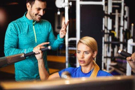 Photo pour Belle femme en forme avec son entraîneur de fitness personnel dans le gymnase exercice - image libre de droit