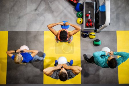 Photo for Group of young fit friends people doing exercises in gym - Royalty Free Image