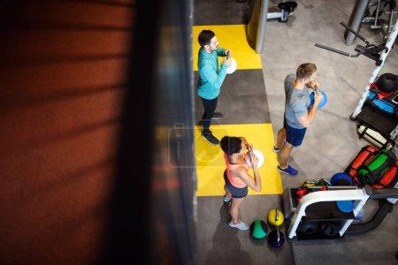 Photo pour Heureux sportifs amis travaillant ensemble avec des cloches de bouilloire dans une salle de gym. - image libre de droit
