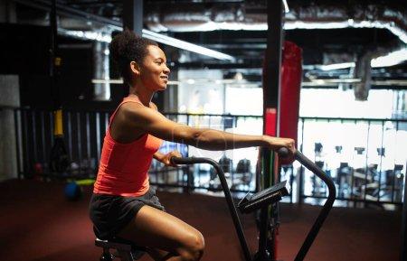 Photo pour Femme de remise en forme à vélo faisant de l'exercice cardio au gymnase. Convient aux jeunes femmes faisant de l'exercice sur un vélo de gym. - image libre de droit