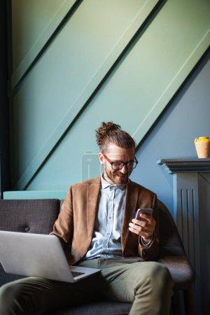 Photo pour Heureux jeune homme d'affaires qui travaille avec un ordinateur portable au bureau - image libre de droit