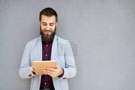 Photo pour Portrait de jeune homme d'affaires tenant la tablette dans les mains en plein air - image libre de droit