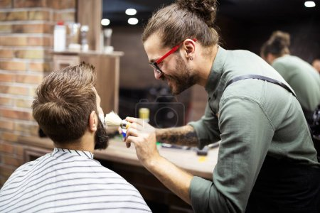 Photo for Handsome man during beard and moustache grooming in barber shop - Royalty Free Image