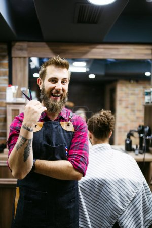 Photo for Barber man in an apron with arms crossed and happy in barber shop - Royalty Free Image