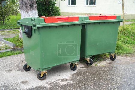 Big green recycling containers on the street.