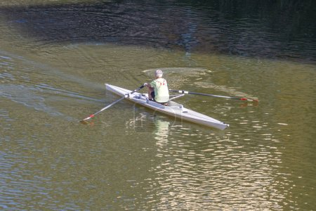 A person rowing boat on Arno River, Florence, Italy.
