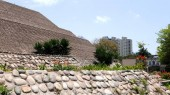 Partial view of the pyramid called Huaca Huallamarca located in San Isidro district of Lima. The temple is circa 2000 years old. Plants, flowers, trees, modern houses and buildings are in the image