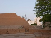 Partial view of the pyramid called Huaca Huallamarca with circa 2000 years old.  Modern buildings are in the image. The photo was taken jus before sunset time