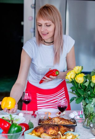 Young woman cooking a dinner for family at kitchen. Roses on a table