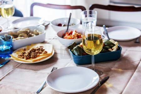 Photo for Glass of wine and dishes on table in dinner time - Royalty Free Image