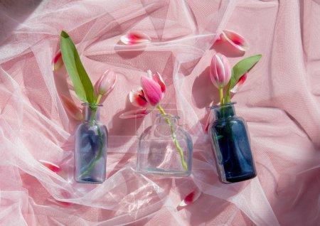 Photo pour Tulipes et botle de verre sur tulle rose. lumière naturelle - image libre de droit