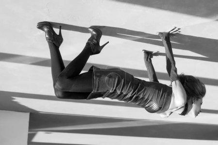 Photo pour Femme dans une pièce abandonnée avec de longues ombres. Image renversée surréaliste en noir et blanc - image libre de droit